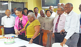Ms Barnett is assisted in cutting her cake by Acting CMO Dr Marion Ducasse. Members of Council look on